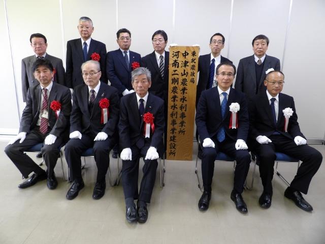 松尾局長(前列右から2人目)ら関係者が看板掲示式で記念撮影した
