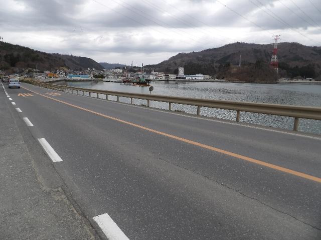 石巻女川線の現道。海側の道路より低い位置をJRの線路が並走している。ここから浦宿橋を架ける。海上では下部工の一部が施工中