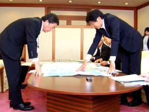 地図を前に高田局長(右)から県内の直轄事業について説明を受ける村井知事