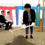 鍬を入れる日本アムウェイ財団の池部事務局長