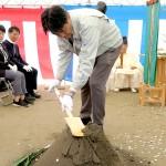 鋤を入れるクマケー建設の熊谷社長