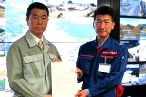 村井知事(左)が代行要請書を佐藤局長に手渡した