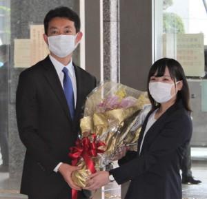 県職員から花束を受け取る熊谷知事(左)